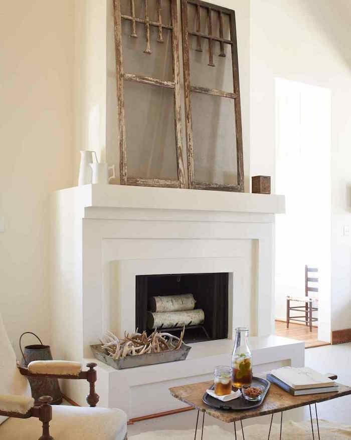 moderniser une cheminée dans déco salon minimaliste avec manteau blanc carré, fenetre bois vintage comme objets décoration, meubles retro en bois rustique