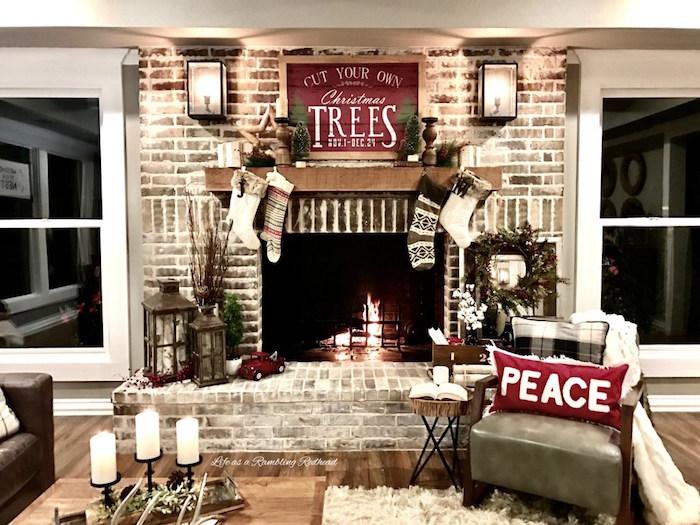 déco pour cheminée en briques sue thème noel avec chaussettes suspendues pour cadeau, cadre bois palettes rouge américain, couronne de gui
