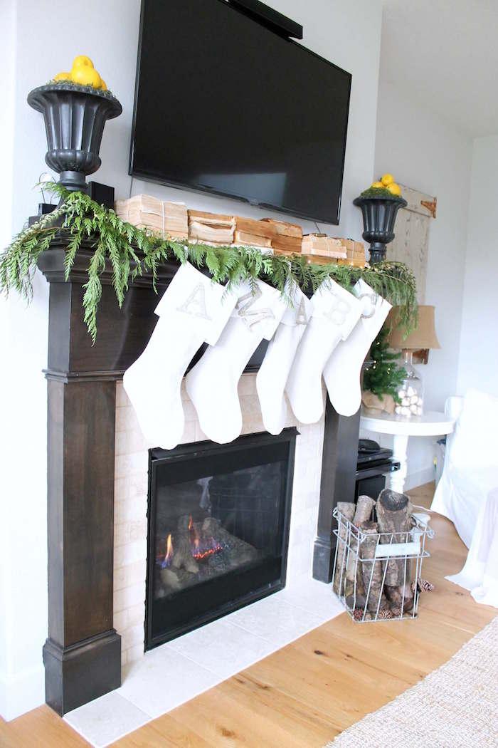 habillage cheminée avec manteau en bois foncé et cadre en briques blanches avec objets déco noel, souliers blancs suspendus et tapis de sapin