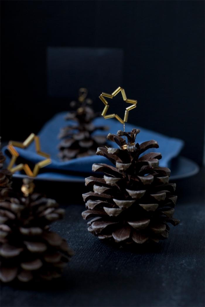 comment faire une déco originale de table de noel, objet décoratif à design sapin en pomme de pin avec petite étoile dorée