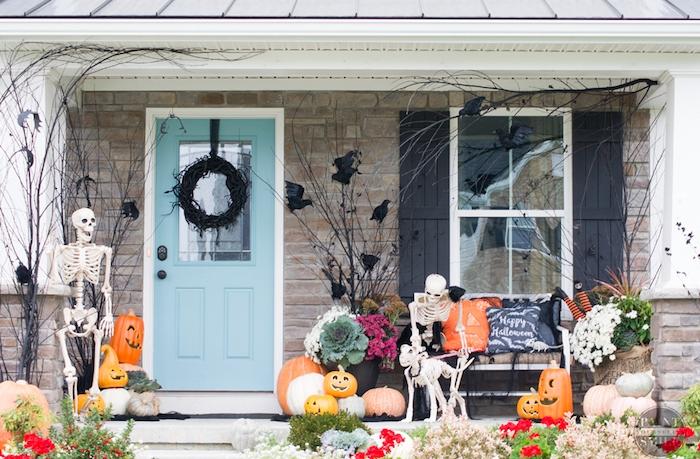 exemple de décoration halloween extérieur a fabriquer, squelettes, jack o lantern citrouille halloween qui fait peur, couronne halloween noire et corbeaux artificiels