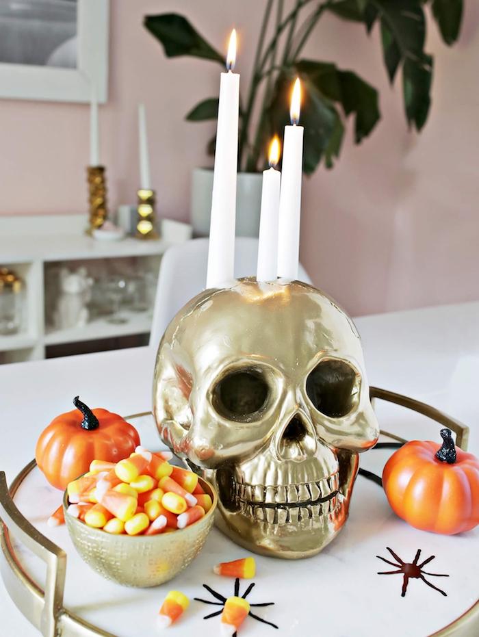 idee de centre de table halloween en crane couleur or, potirons orange artificielles, bonbons halloween, deco halloween fait maison