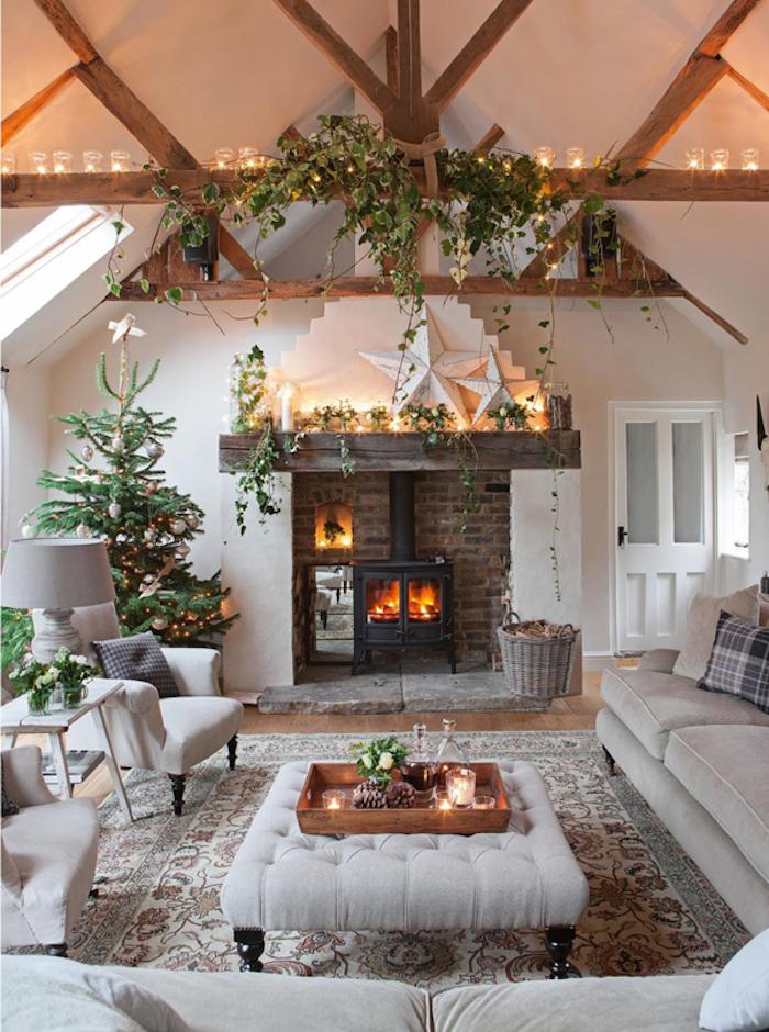 salon mansardé rustique scandinave avec déco de noel et cheminée en briques avec poele à bois, poutres apparentes canapé velours gris et feuillages décoratifs