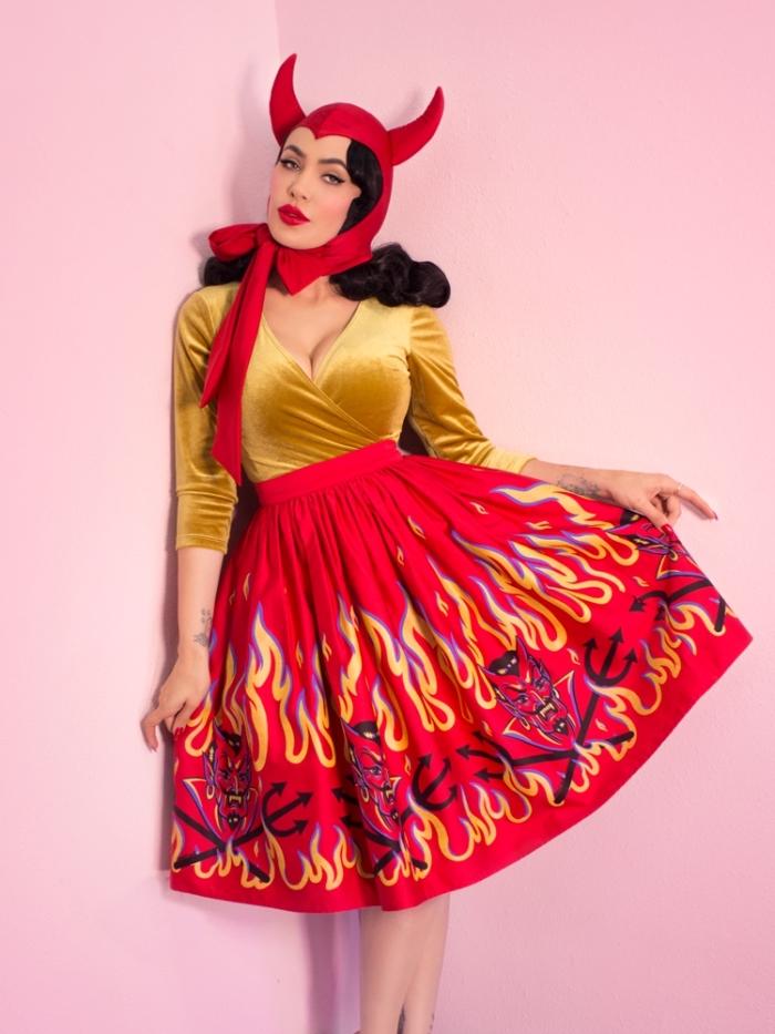 déguisement diablesse rétro chic composé d'une jupe évasée imprimé diable, blouse cache-coeur en velours et un chapeau avec cornes, look original de diablesse pin up