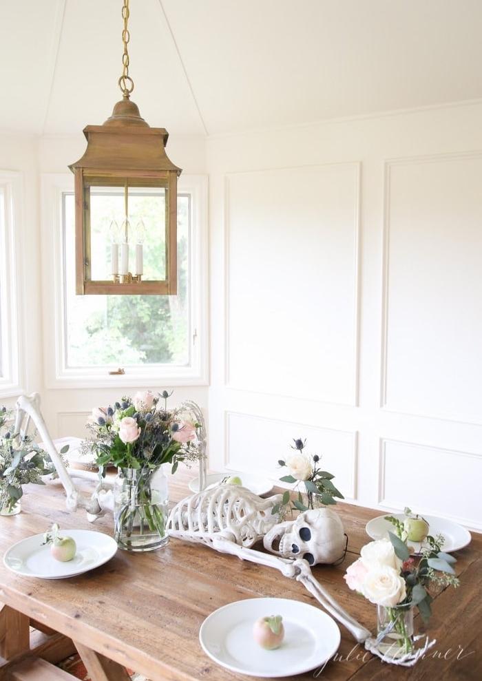 deco halloween maison originale, table style rustique décorée de bouquets de fleurs et une squelette de mort