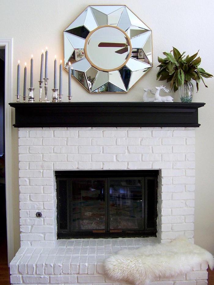 cheminée avec manteau en briques repeintes en blanc et support noir mat avec chandelier et bougies, miroir chrome design sur mur blanc