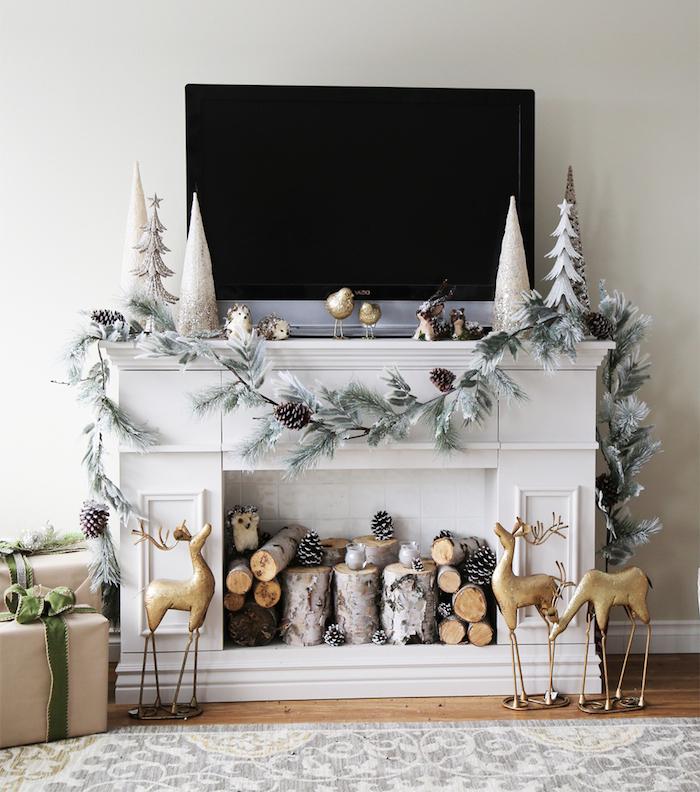 relooker une fausse cheminée décorative avec manteau blanc et fond en carrelage, objets déco noel avec petites buches, guirlande pommes de pain, rênes dorés