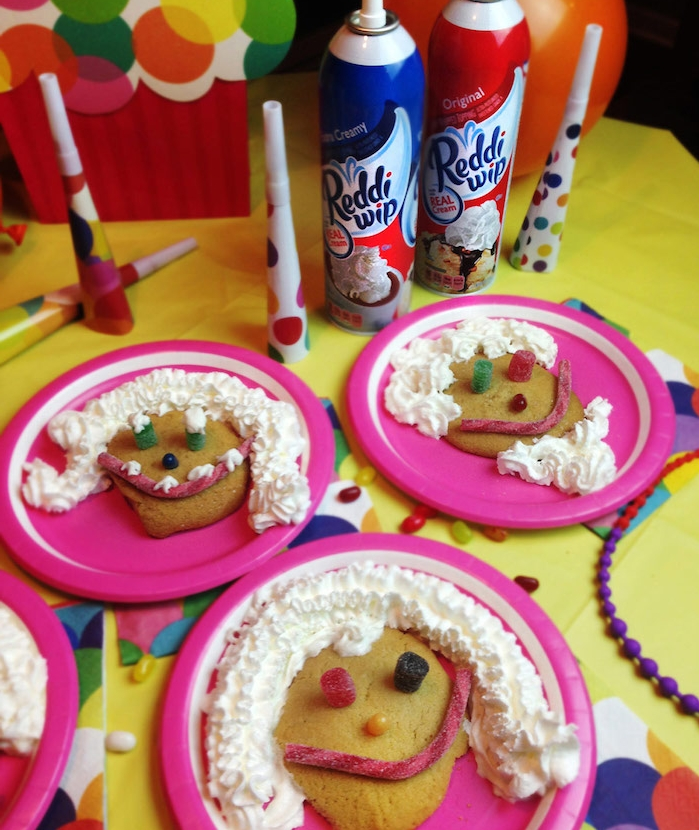 decoration biscuit original avec de la crème fraîche, dragées, gélifiés et autres bonbons dans une assiette rose