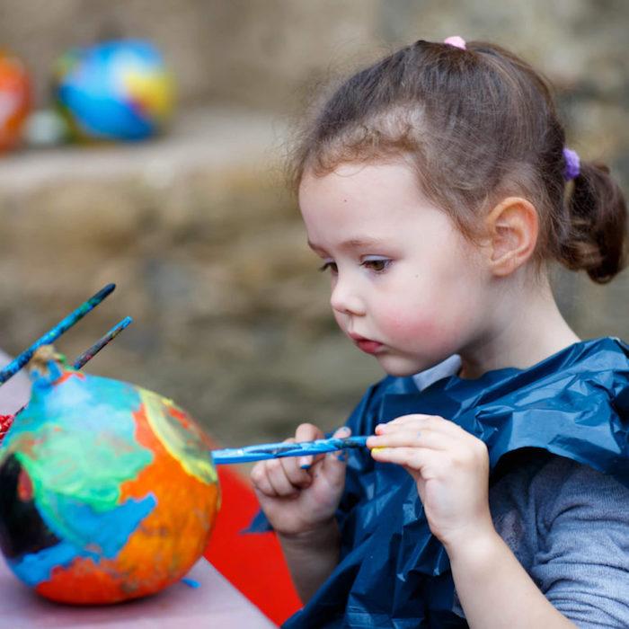 idée animation anniversaire pour l automne, dessins su citrouille avec de la peinture acrylique, petite fille qui dessine