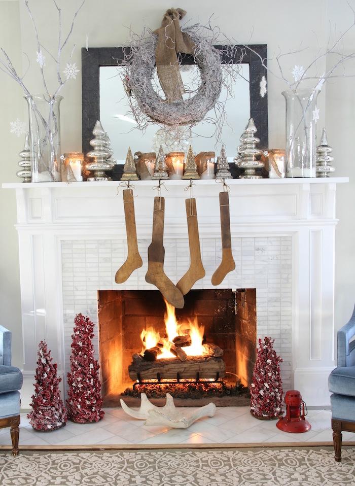manteau de cheminée blanc à cadre en mosaique type crédence et déco sur thème hiver et noel avec objets décoratifs comme souliers en bois, min sapins rouges et bougeoirs design chrome et couronne grise