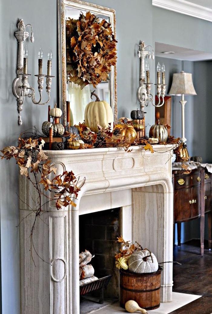 décoration d'automne pour cheminée avec cadre type antique sur mur gris avec feuilles sèhes et artificielles et citrouille et objets déco couleur cuivre