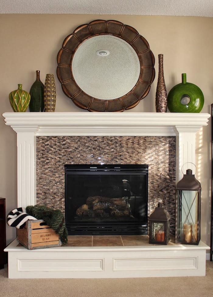 cheminée décorer simplement avec objets deco caisse en bois miroir en métal et vases design en terre cuite, lanterne à bougies