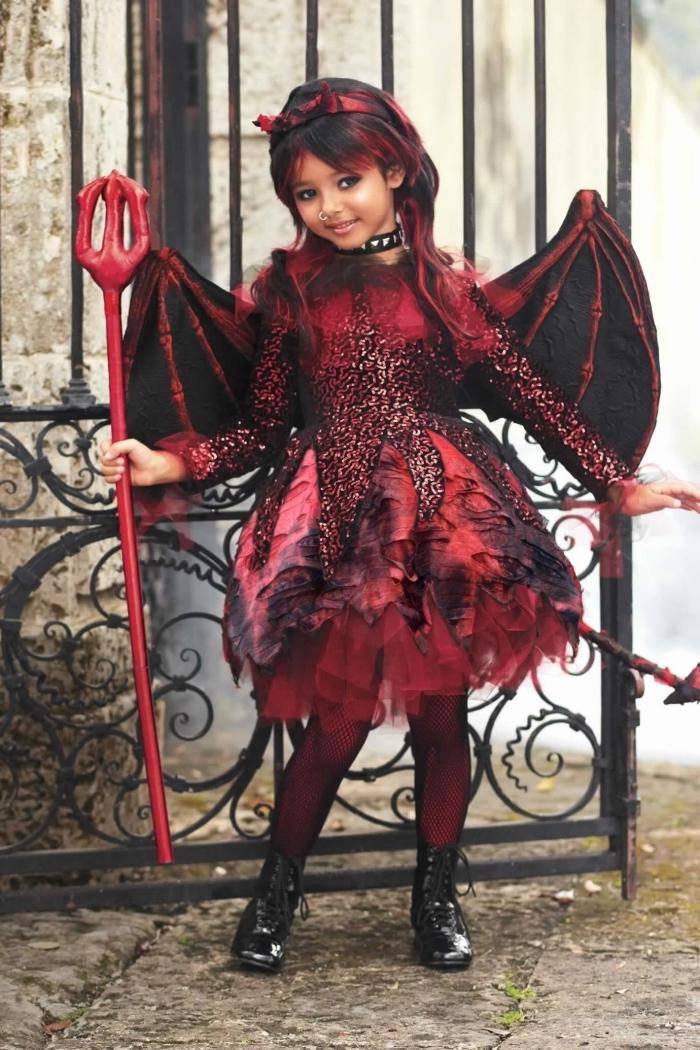 costume de petite diablesse gothique composé d'un robe à sequins et tulle à jupe tutu, paire d'aile et une fourche de diable, idée de deguisement halloween fille en petit diable gothique