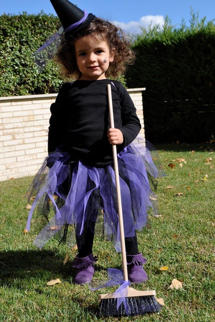 petite fille sorcière en blouse noire, jupe en tulle violette, chapeau sorcière pointu, balai simple, idée mignonne petite sorcière