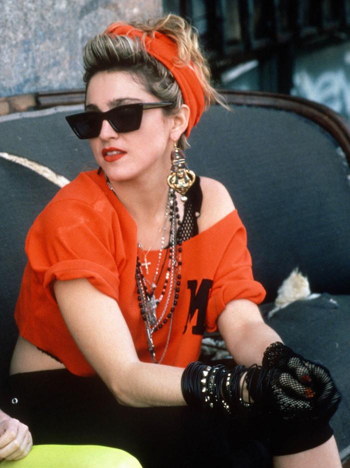 Look année 80, vêtements d'occasion musique populaire glamour look de Madonna avec une tee-shirt épaule dénudée, lunettes de soleil, bandana