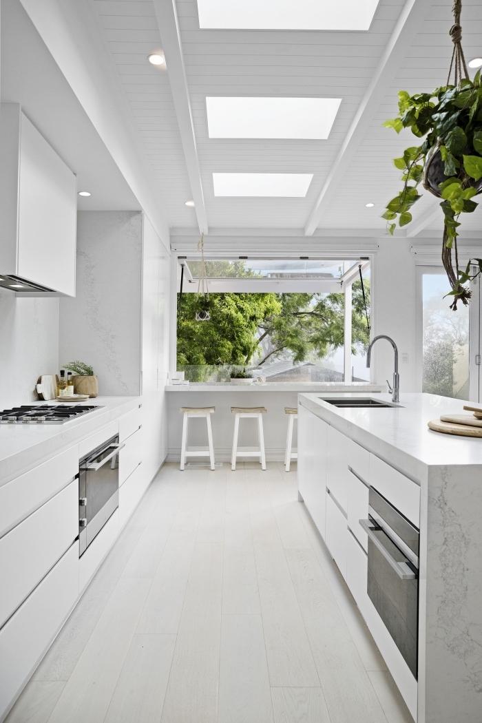 décoration épurée dans une cuisine ouverte équipée d'îlot avec évier et plan de travail à design marbre blanc