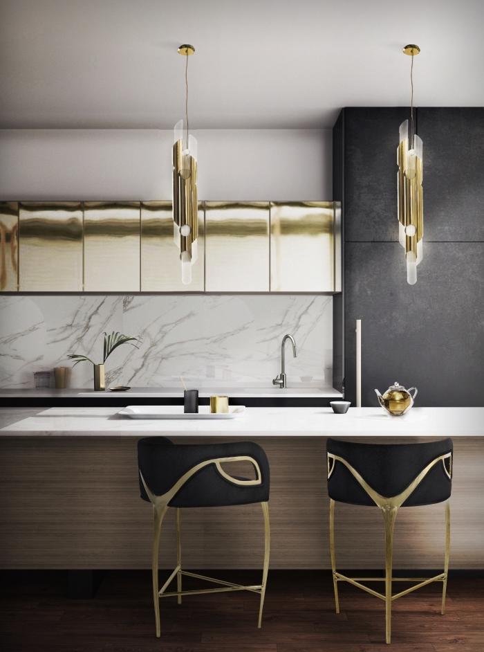 cuisine aménagée avec crédence en marbre blanc et meubles haut à design métallique doré, modèle d'îlot bi matière en beige et blanc