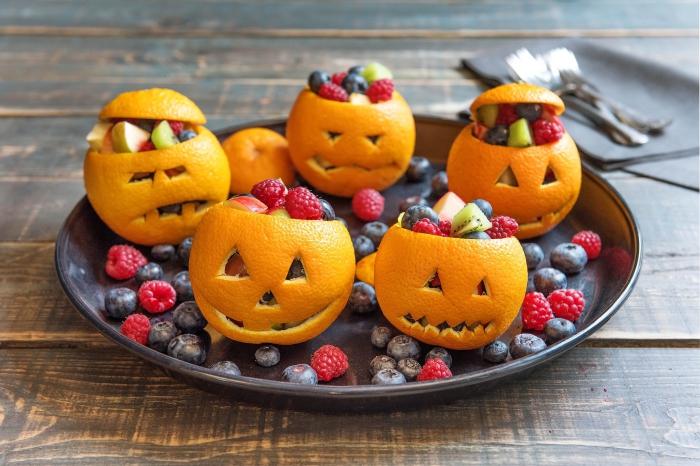 idée pour un dessert d'halloween santé, des bols citrouilles d'halloween réalisés avec des oranges, remplis de fruits rouges