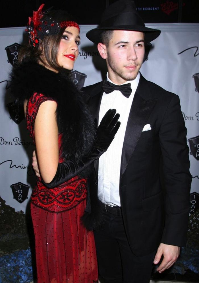 homme en costume habillé, chemise blanche, papillon, chapeau noir, femme robe rouge, gants longs noirs, accessoire de cheveux