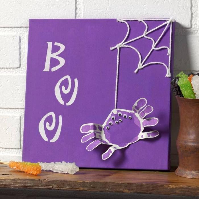 déco d'halloween originale de tableau violet avec toile d'araignée en fils de laine et une araignée empreinte de main, activité manuelle primaire ludique et créative sur le thème d'halloween