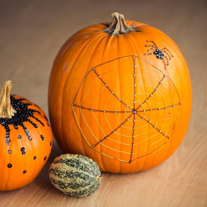 citrouille halloween avec déco minimaliste en fil et paillettes, idée comment décorer une citrouille avec matériaux récyclés