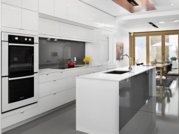 cuisine blanche moderne avec crédence en gris anthracite, modèle d'îlot central bicolore blanc et gris avec évier