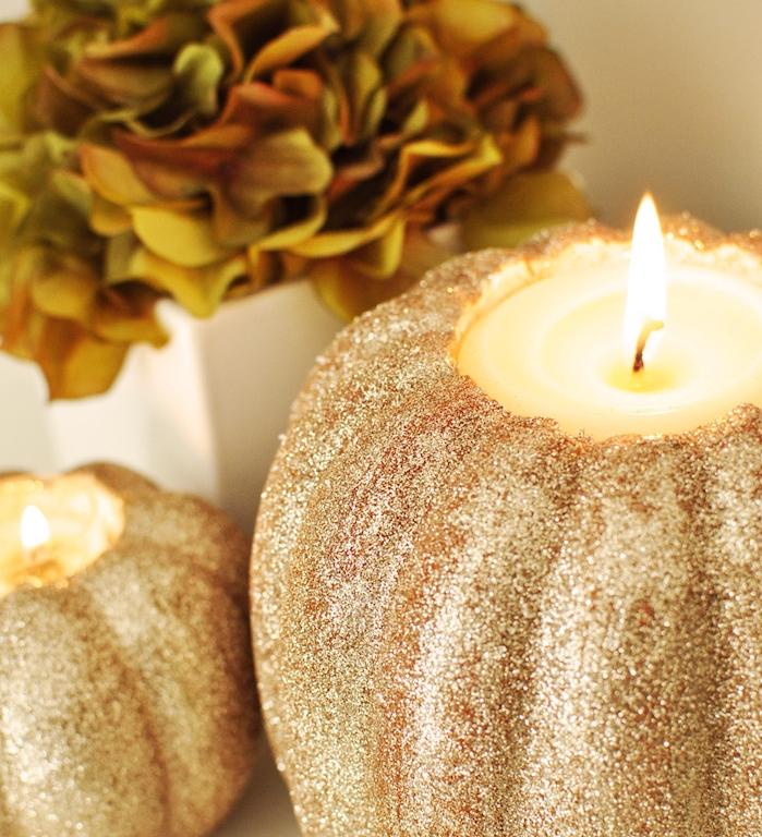 bricolage halloween facile en citrouille décorée de paillettes avec une bougie à l intérieur et un bouquet de fleurs à côté