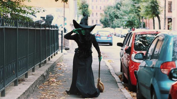la sorcière d oz coloration visage et corps ver, robe sorcière traditionnelle longue noire, balai et chapeau de sorciere