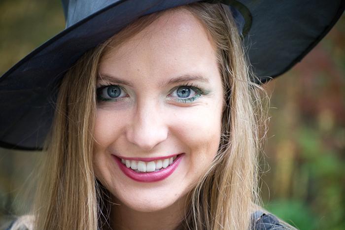 réussir son maquillage de sorcière avec un rouge à lèvres rouge, ombres paupières vertes et mascara, femme chapeau de sorcière noire