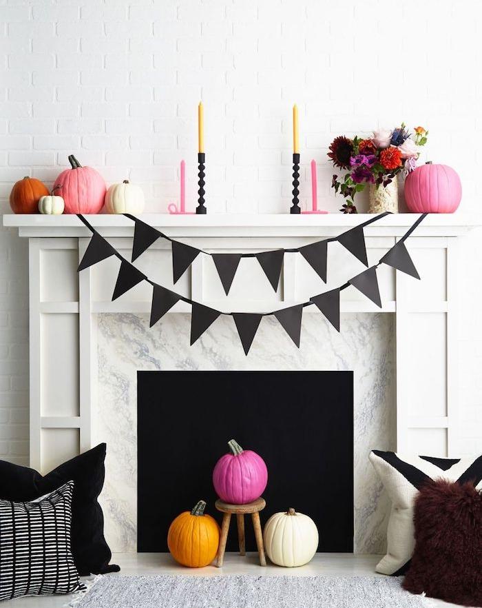 deco halloween a faire soi meme, citrouilles repeintes de couleur orange, rouge et blanc, avec une guirlande fanion, bougeoir et bouquet de fleurs