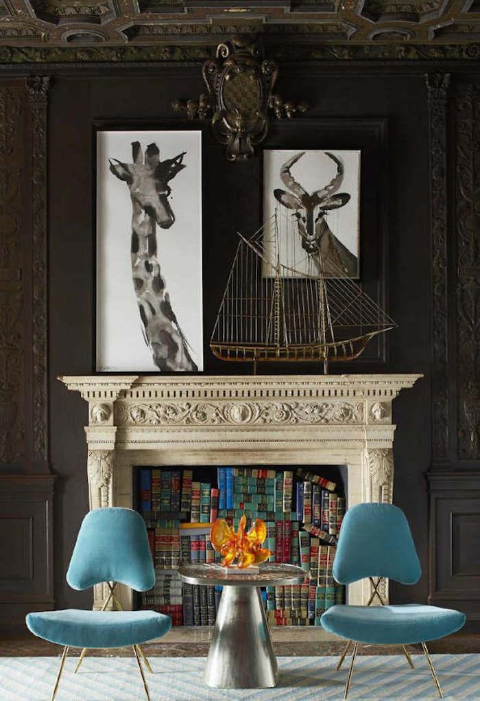 photo fausse cheminée décorative taillée comme support déco livres anciens maquette bateau, chaises retro en velours bleu
