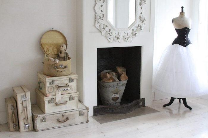 fausse cheminée décorative blanches avec objets retro seau metal avec buches dans foyer, collection anciennes valises