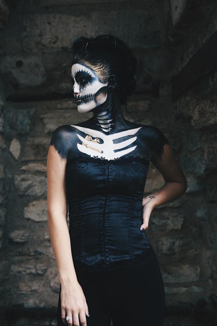 femme au maquillage halloween squelette habillée en noir, visage demi crâne