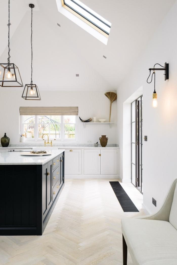exemple de cuisine blanche avec comptoir en marbre blanc et îlot central aux armoires noires avec poignées dorées