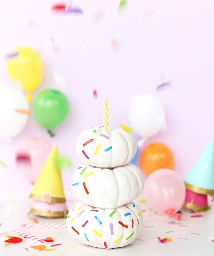 deco halloween fait maison en citrouilles décorées de peinture blanche avec traits colorés, fond deco de fete en ballons et chapeau d anniversaire