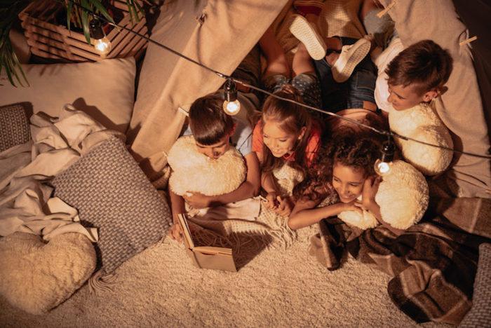 une soirée pyjama fête originale dans un tipi avec surplombé de guirlande lumineuse, enfants faisant une lecture collective