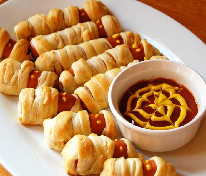 des saucisses momies enrobées de pâte feuilletée en amuse-bouches originaux, servies avec de la sauce tomate en toile d'araignée