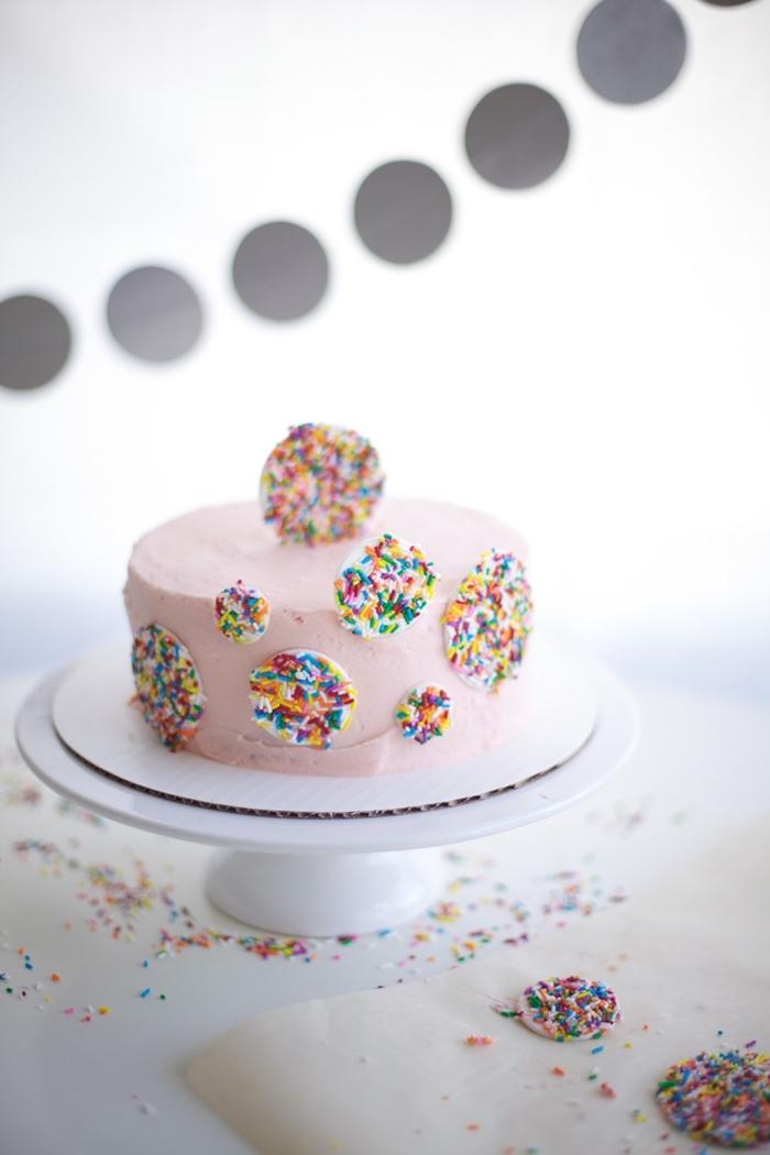 gâteau au glaçage rose à motifs pois design polka dot réalisés en pâte de gomme prête à l'emploi recouverte de vermicelles colorées
