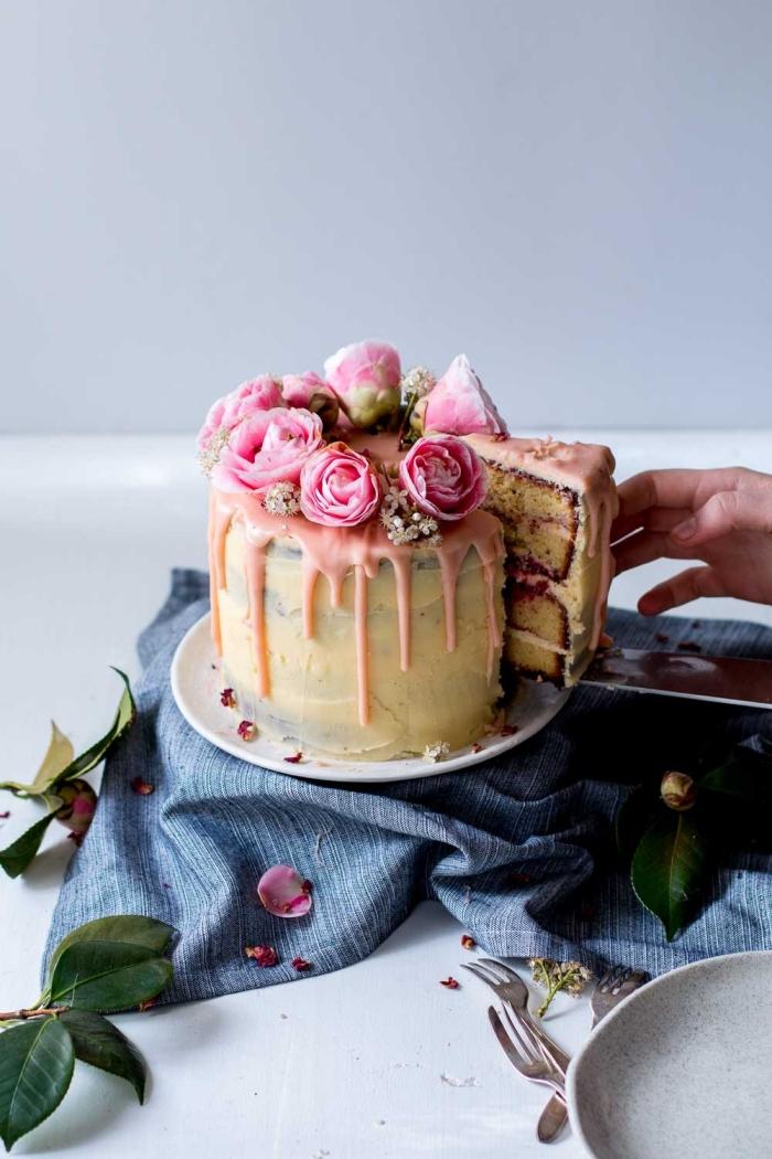 joli gâteau d'anniversaire aux amandes et aux framboises, parfumé au citron, avec un coulis de chocolat blanc coloré rose et un nappage gâteau à la crème au beurre et au fromage frais