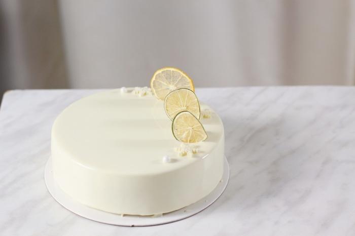 idée pour un gâteau design élégant au glacage miroir chocolat blanc, décoré de tranches de citron