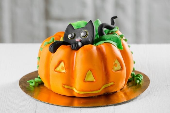 recette d halloween effrayante, modèle de gâteau citrouille réalisé avec fondant coloré en orange et petites figurines en sucre