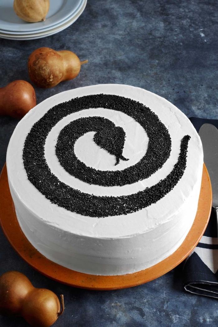 idée repas halloween ou dessert facile de dernière minute, modèle de gâteau à glaçage blanc avec déco en sucre noir design serpent