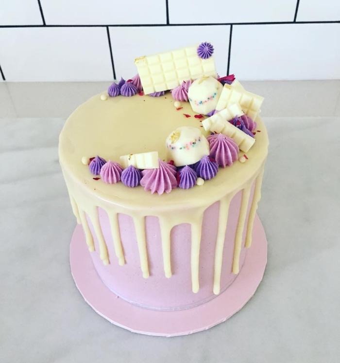 glacage blanc coulant au chocolat fondu sur une base de crème au beurre rose, gâteau dégoulinant au coulis de chocolat blanc, décoré avec des roses en glaçage et des morceaux de chocolat