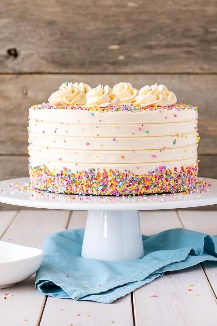 un gâteau d'anniversaire recouvert de glacage blanc vanille au beurre saupoudré de vermicelles colorées