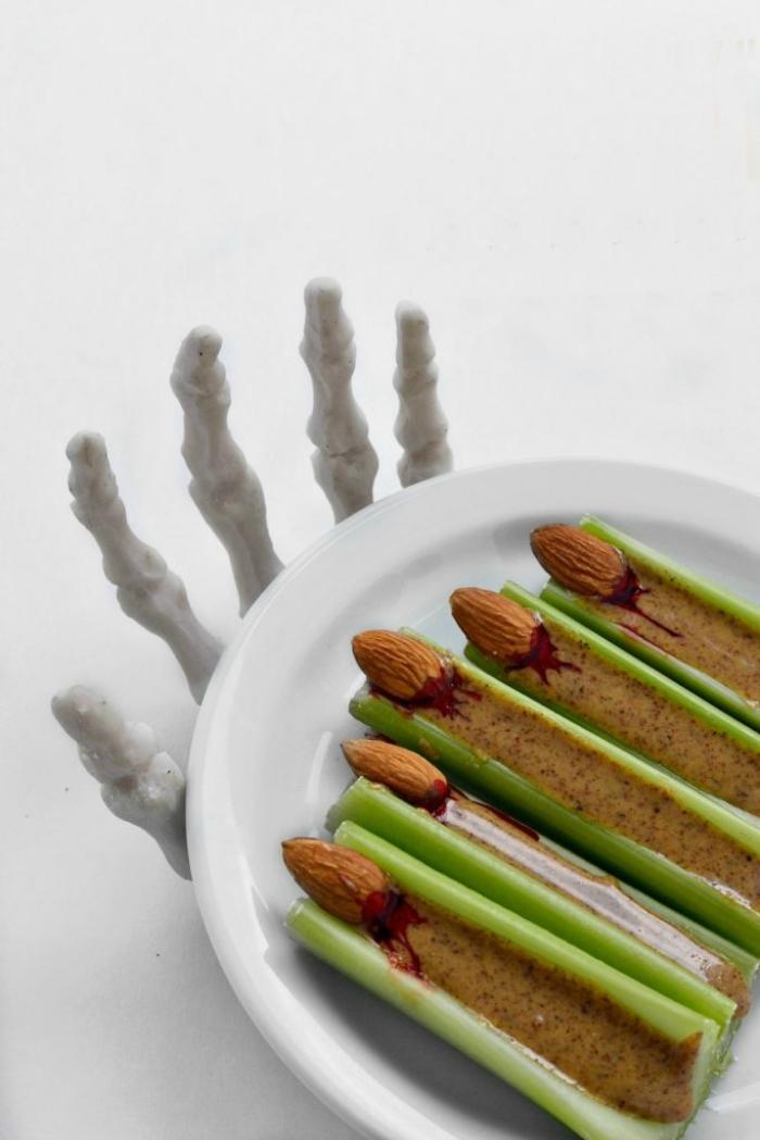 recette facile d'apero dinatoire halloween, des bâtonnets de céleri au beurre d'amande imitant les doigts de sorcière sur un dessous-de-plat main de squelette