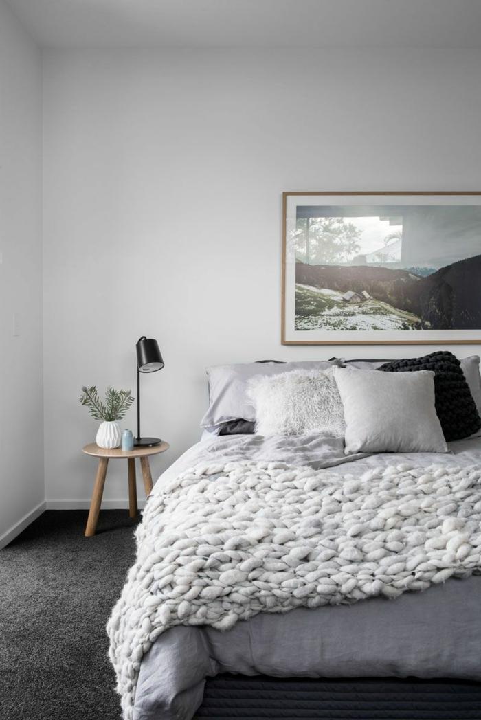 plaid grosse maille, peinture murale gris clair, tabouret en bois, lampe de table noire, grand paysage encadré, tapis gris, coussins