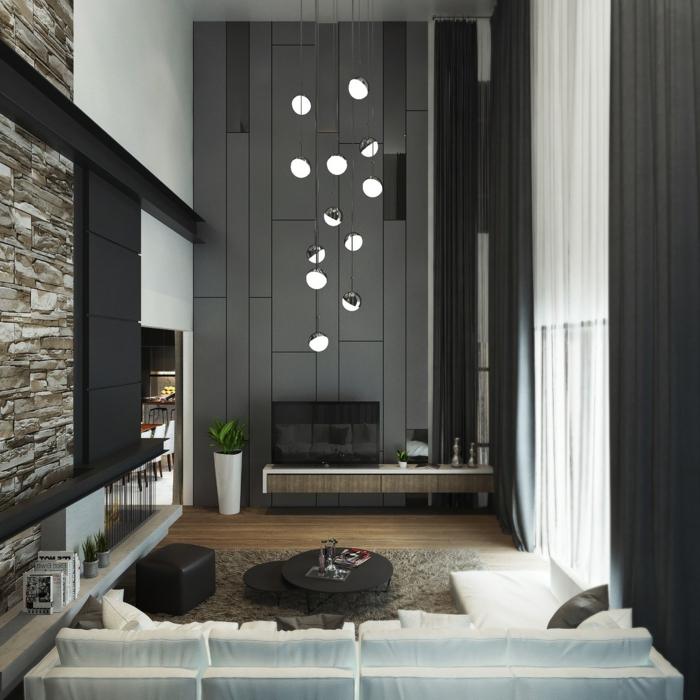 quel mur peindre en foncé pour agrandir la pièce, suspensions, petites tables noires, mur en pierre, sofas blancs