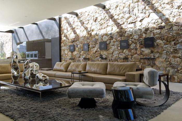 grand salon design avec mur en pierre intérieur et faux plafond avec poutres apparentes et grand canapé en cuir beige