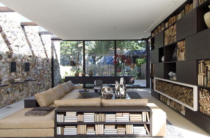 salon design rustique et moderne avec grand mur en pierre d'origine et faux plafond avec poutres semi apparentes