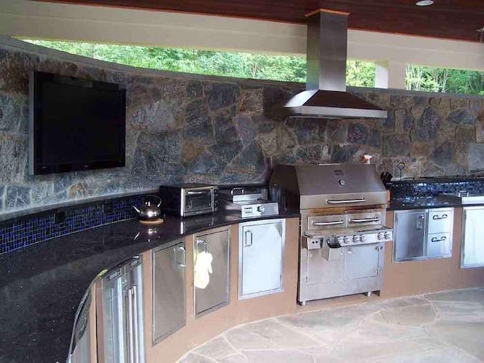 cuisine d'extérieur en arc de cercle avec plan de travail et four grill en inox pour jardin d'été